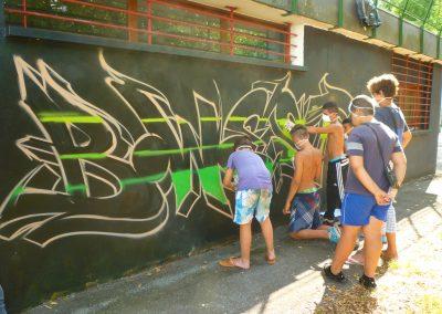 Graffiti Street Art En action sur le mur du foyer dans le quartier du Biollay