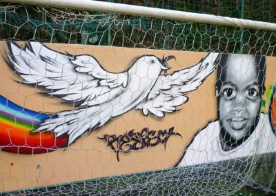 Graffiti Street Art Intervention et décoration avec l'artiste Fazer sur le mur du terrain de football à Valbonne en 2010 Thématique : Paix et Unité
